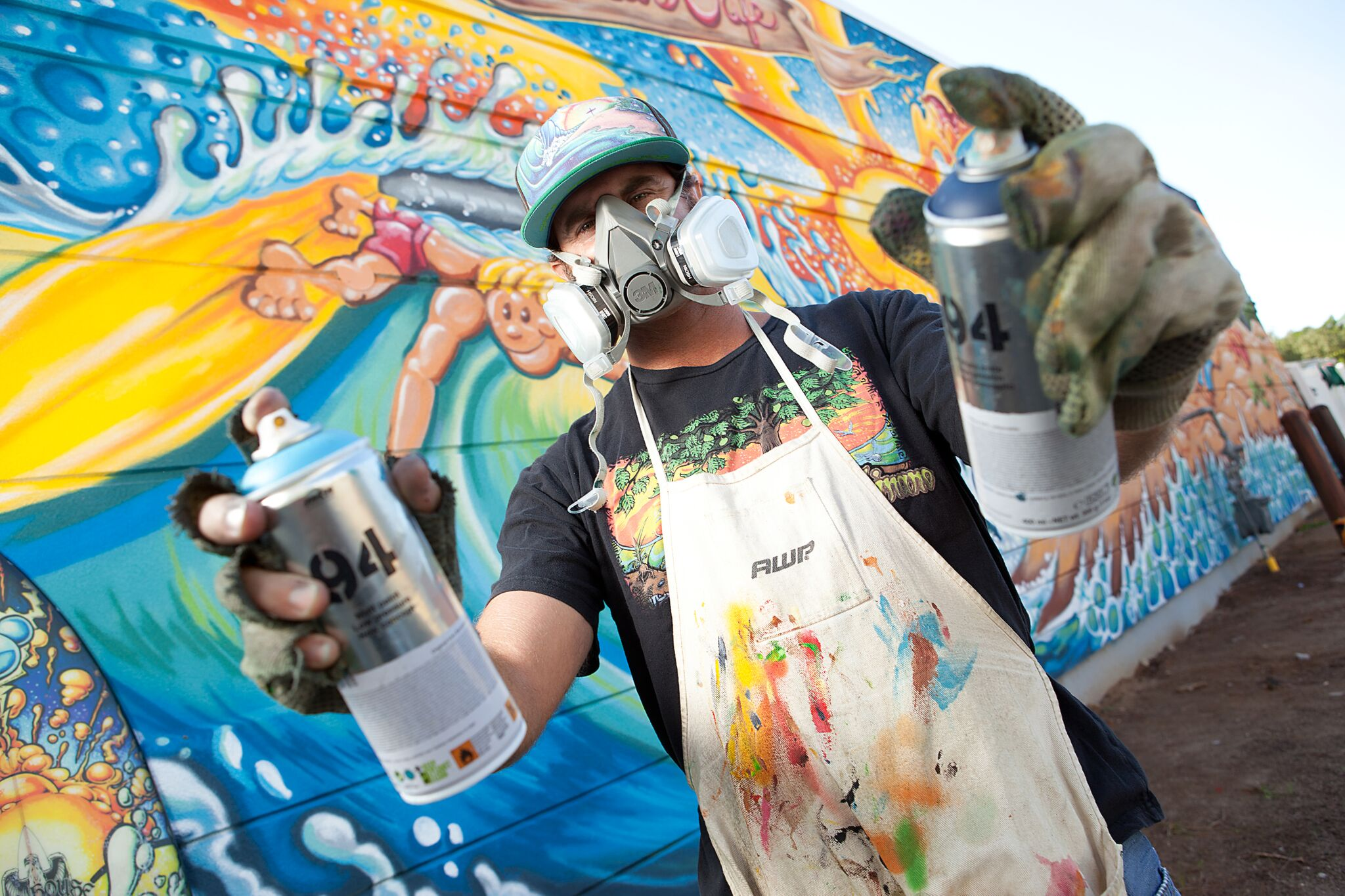 Drew Brophy holding spray paint cans Photo by Scott Smallin preview